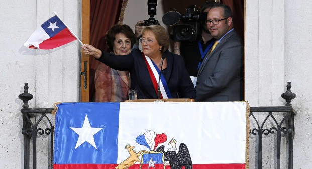 Chile's new president Michelle Bachelet waves a Chilean flag from a balcony of the La Moneda presidential palace after being sworn into office, in Santiago