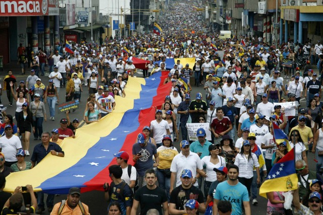 Opposition supporters hold a national a flag during a rally against Nicolas Maduro's government in San Cristobal